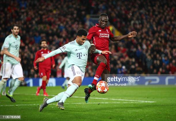 Sadio Mane of Liverpool battles with Serge Gnabry of Bayern Munich during the UEFA Champions League Round of 16 First Leg match between Liverpool and...