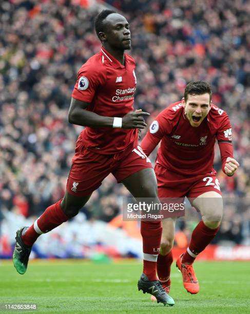 Sadio Mane of Liverpool celebrates after scoring his team's first goal with Andy Robertson during the Premier League match between Liverpool FC and...