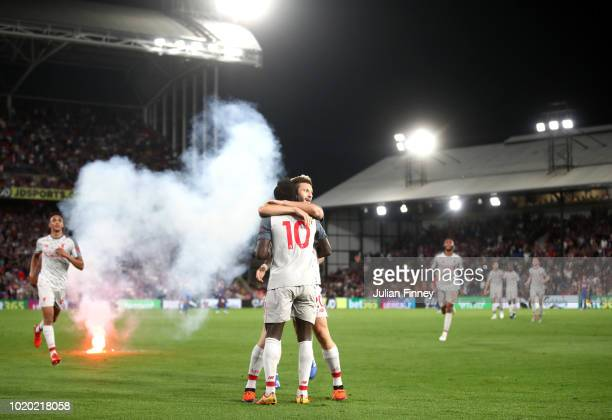 Sadio Mane of Liverpool celebrates after scoring his team's second goal with team mate Adam Lallana during the Premier League match between Crystal...