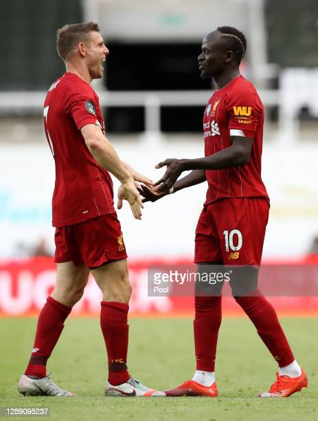 Sadio Mane of Liverpool celebrates after scoring his team's third goal with James Milner during the Premier League match between Newcastle United and...