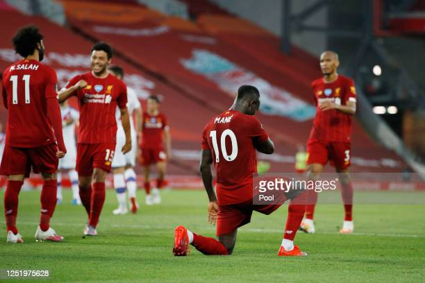 Sadio Mane of Liverpool celebrates by taking a knee after he scores his sides fourth goal during the Premier League match between Liverpool FC and...