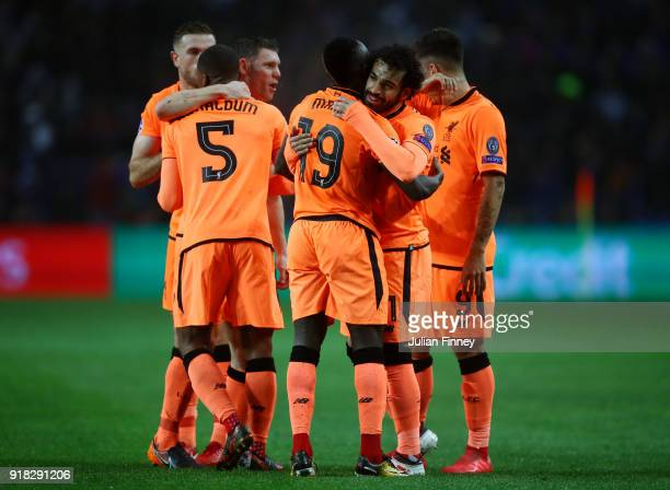 Sadio Mane of Liverpool celebrates scoring the first goal with team mates during the UEFA Champions League Round of 16 First Leg match between FC...