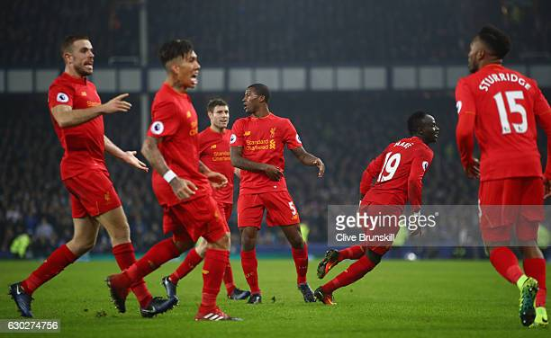 Sadio Mane of Liverpool celebrates with his team mates after scoring the winning goal in injury time during the Premier League match between Everton...