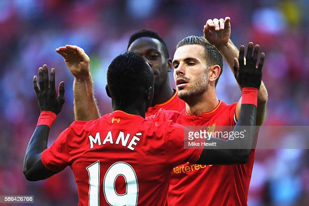 Sadio Mane of Liverpool celebrates with Jordan Henderson of Liverpool after the own goal scored by Javier Mascherano of Barcelona during the...