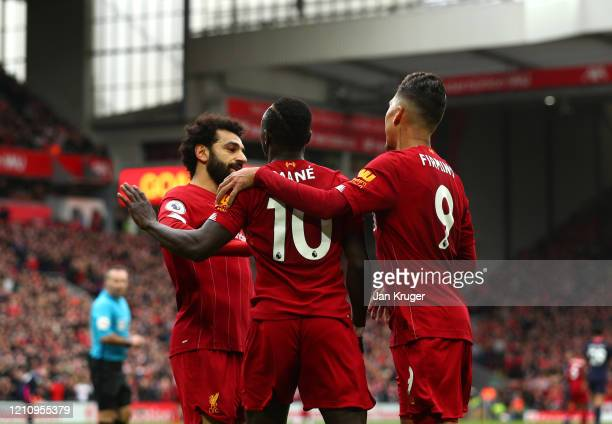 Sadio Mane of Liverpool celebrates with Mohamed Salah and Roberto Firmino after scoring his team's second goal during the Premier League match...