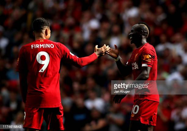 Sadio Mane of Liverpool celebrates with Roberto Firmino after he scores his team's second goal during the Premier League match between Liverpool FC...