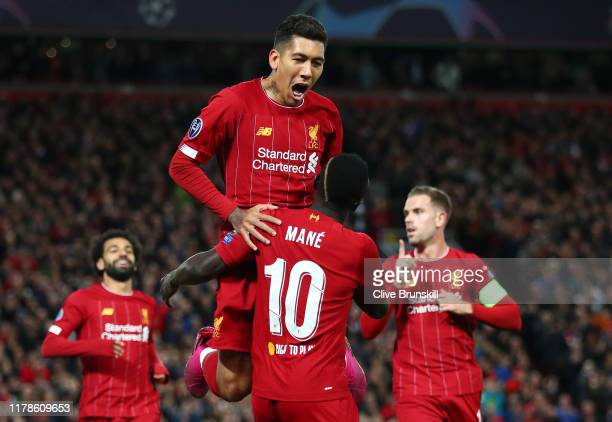 Sadio Mane of Liverpool celebrates with Roberto Firmino after scoring his sides first goal during the UEFA Champions League group E match between...
