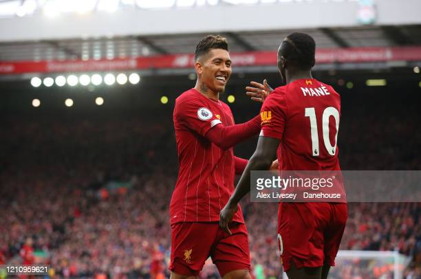 Sadio Mane of Liverpool celebrates with Roberto Firmino after scoring their second goal during the Premier League match between Liverpool FC and AFC...