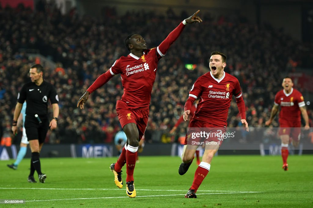 Sadio Mane of Liverpool celebrates with team mate Andy Robertson after scoring the third Liverpool goal during the Premier League match between Liverpool and Manchester City at Anfield on January 14, 2018 in Liverpool, England.