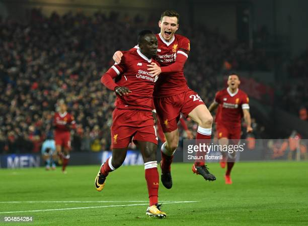 Sadio Mane of Liverpool celebrates with team mate Andy Robertson after scoring the third Liverpool goal during the Premier League match between...