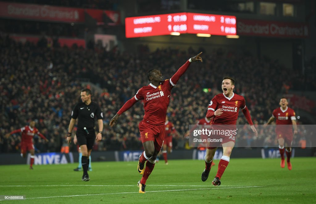 Sadio Mane of Liverpool celebrates with team mate Andy Robertson after scoring the third Liverpool goal during during the Premier League match between Liverpool and Manchester City at Anfield on January 14, 2018 in Liverpool, England.