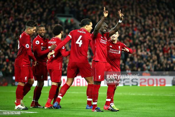 Sadio Mane of Liverpool celebrates with team mates after scoring his sides third goal during the Premier League match between Liverpool FC and...