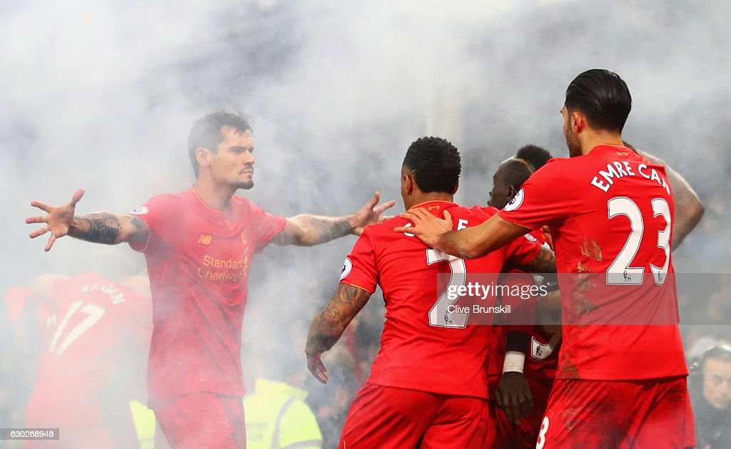 Sadio Mane of Liverpool (19) celebrates with team mates as he scores their first goal during the Premier League match between Everton and Liverpool at Goodison Park on December 19, 2016 in Liverpool, England.