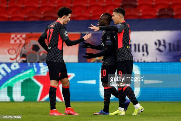 Sadio Mane of Liverpool celebrates with team mates Curtis Jones and Roberto Firmino after scoring their side's second goal during the UEFA Champions...