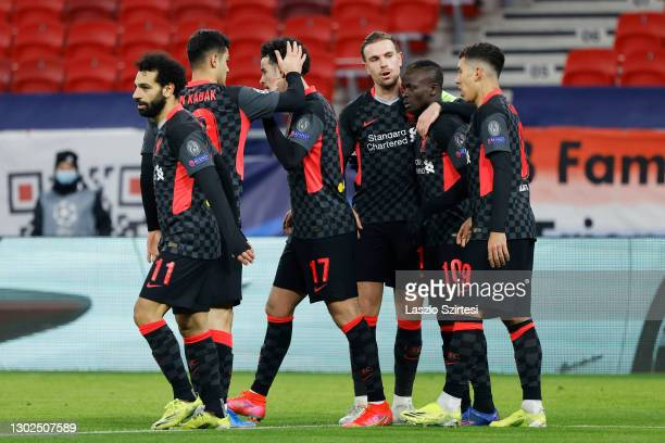 Sadio Mane of Liverpool celebrates with team mates Jordan Henderson and Roberto Firmino after scoring their side's second goal during the UEFA...