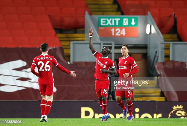 Sadio Mane of Liverpool celebrates with teammate Roberto Firmino and Andy Robertson after scoring their team's first goal during the Premier League...