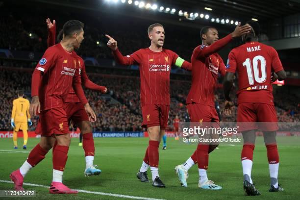 Sadio Mane of Liverpool celebrates with teammates including Jordan Henderson of Liverpool and Georginio Wijnaldum of Liverpool after scoring their...