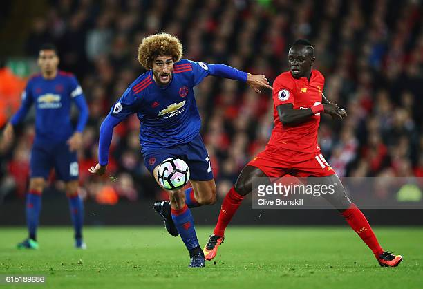Sadio Mane of Liverpool challenges Marouane Fellaini of Manchester United during the Premier League match between Liverpool and Manchester United at...