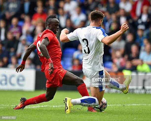 Sadio Mane of Liverpool competes with Liam Ridehalgh of Tranmere Rovers during a PreSeason Friendly match between Tranmere Rovers and Liverpool at...