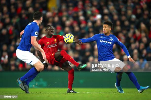 Sadio Mane of Liverpool controls the ball under pressure from Mason Holgate and Michael Keane of Everton during the Premier League match between...