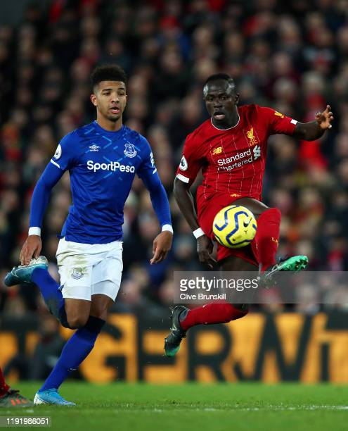 Sadio Mane of Liverpool controls the ball under pressure from Mason Holgate of Everton during the Premier League match between Liverpool FC and...