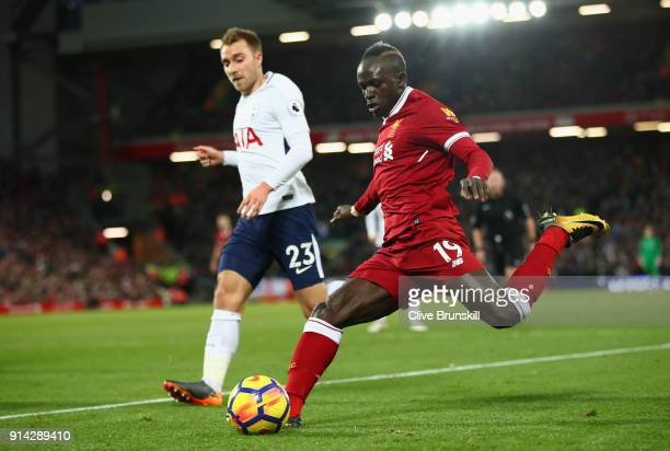 Sadio Mane of Liverpool crosses the ball under pressure from Christian Eriksen of Tottenham Hotspur during the Premier League match between Liverpool...