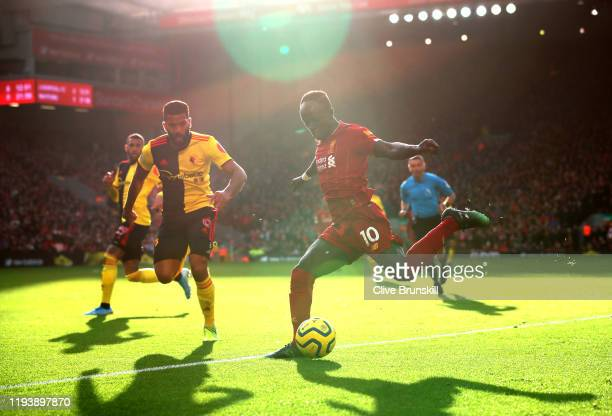 Sadio Mane of Liverpool crosses under pressure from Adrian Mariappa of Watford during the Premier League match between Liverpool FC and Watford FC at...