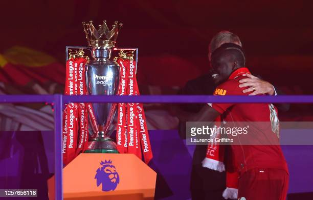 Sadio Mane of Liverpool embraces Sir Kenny Dalglish Former Captain and Manager of Liverpool upon receiving a Premier League Winner's medal following...