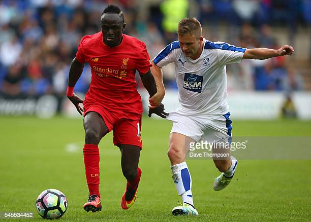 Sadio Mane of Liverpool gets past Jay Harris of Tranmere Rovers during the PreSeason Friendly match between Tranmere Rovers and Liverpool at Prenton...
