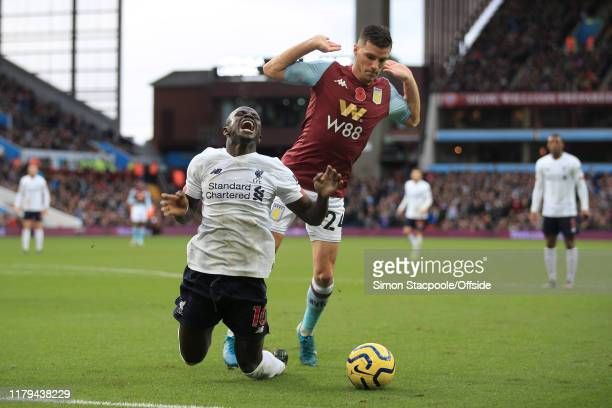 Sadio Mane of Liverpool goes down under a challenge from Frederic Guilbert of Villa but is then booked for diving during the Premier League match...