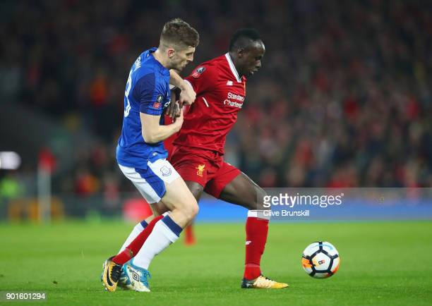 Sadio Mane of Liverpool holds off Jonjoe Kenny of Everton during the Emirates FA Cup Third Round match between Liverpool and Everton at Anfield on...