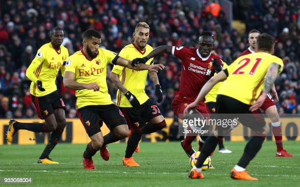 Sadio Mane of Liverpool is challenged by Adrian Mariappa of Watford during the Premier League match between Liverpool and Watford at Anfield on March...