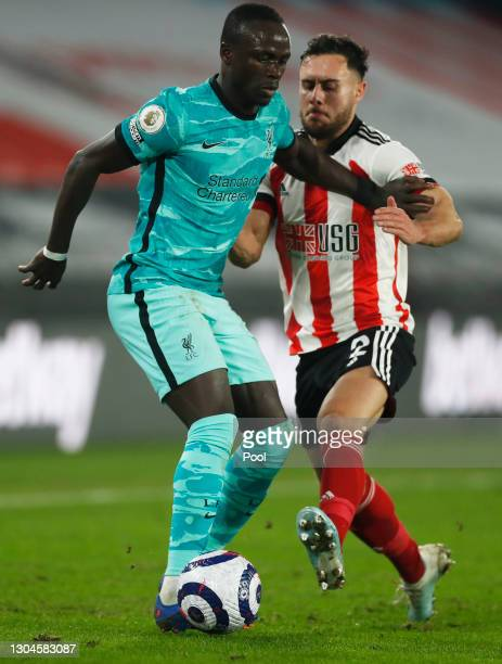 Sadio Mane of Liverpool is challenged by George Baldock of Sheffield United during the Premier League match between Sheffield United and Liverpool at...