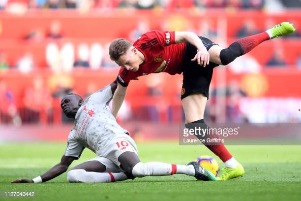 Sadio Mane of Liverpool is challenged by Scott McTominay of Manchester United during the Premier League match between Manchester United and Liverpool...