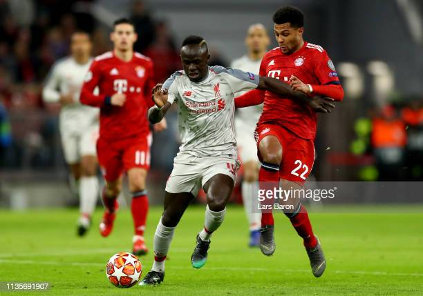 Sadio Mane of Liverpool is challenged by Serge Gnabry of Muenchen during the UEFA Champions League Round of 16 Second Leg match between FC Bayern...