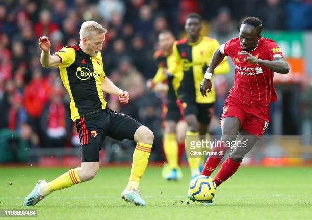 Sadio Mane of Liverpool is challenged by Will Hughes of Watford during the Premier League match between Liverpool FC and Watford FC at Anfield on...