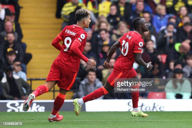 Sadio Mane of Liverpool is chased by Roberto Firmino after scoring their side's first goal during the Premier League match between Watford and...