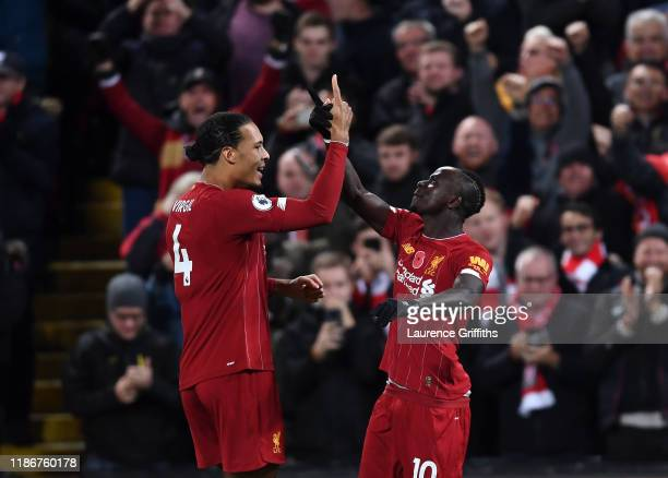 Sadio Mane of Liverpool is congratulated by Virgil Van Dijk after scoring the third goal during the Premier League match between Liverpool FC and...