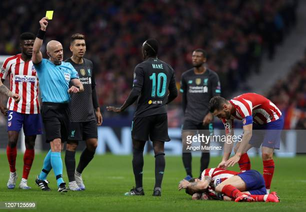 Sadio Mane of Liverpool is shown a yellow card by referee Szymon Marciniak after a foul on Sime Vrsaljko of Atletico Madrid during the UEFA Champions...