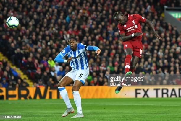 Sadio Mane of Liverpool scores his team's second goal as Terence Kongolo of Huddersfield Town challenges during the Premier League match between...