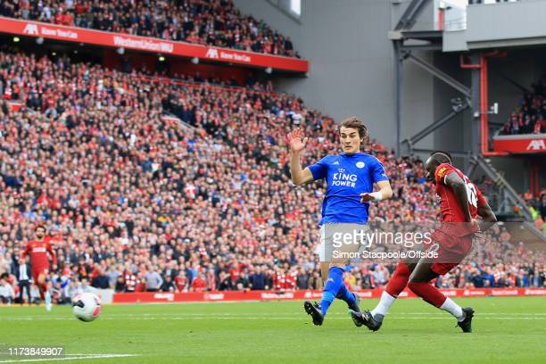 Sadio Mane of Liverpool scores their 1st goal past Caglar Soyuncu of Leicester during the Premier League match between Liverpool FC and Leicester...