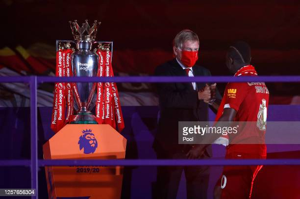 Sadio Mane of Liverpool shakes hands with Sir Kenny Dalglish Former Captain and Manager of Liverpool upon receiving a Premier League Winner's medal...