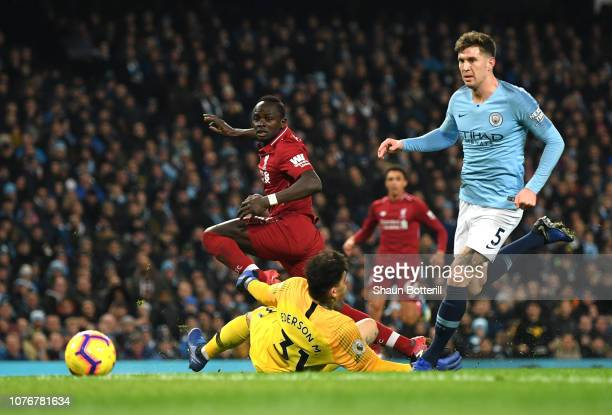 Sadio Mane of Liverpool shoots past Ederson of Manchester City as John Stones of Manchester City looks on during the Premier League match between...