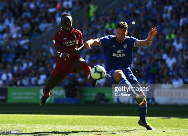 Sadio Mane of Liverpool shoots under pressure from Sean Morrison of Cardiff City during the Premier League match between Cardiff City and Liverpool...