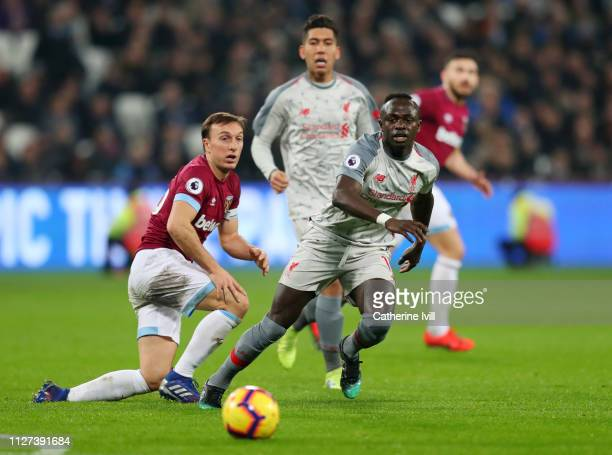 Sadio Mane of Liverpool shoots while challenged by Mark Noble of West Ham United during the Premier League match between West Ham United and...