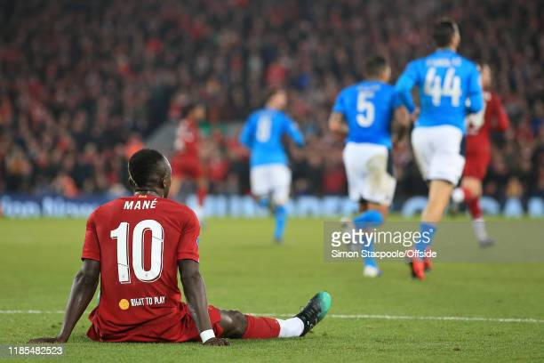 Sadio Mane of Liverpool sits on the floor as play continues during the UEFA Champions League group E match between Liverpool FC and SSC Napoli at...