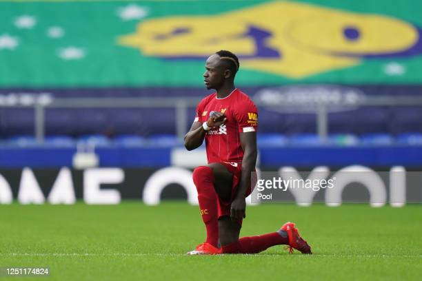 Sadio Mane of Liverpool takes a knee in support of the Black Lives Matter movement during the Premier League match between Everton FC and Liverpool...