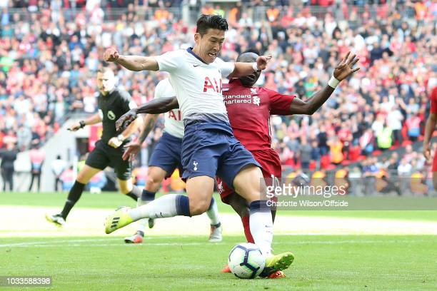 Sadio Mane of Liverpool takes away the standing foot of Heung MinSon of Tottenham in the penalty area during the Premier League match between...