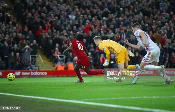 Sadio Mane of Liverpool takes the ball past Dean Henderson of Sheffield United and goes on to score his sides second goal during the Premier League...