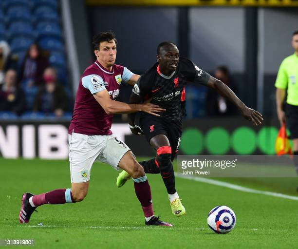 Sadio Mane of Liverpool with Burnley's Jack Cork during the Premier League match between Burnley and Liverpool at Turf Moor on May 19, 2021 in...